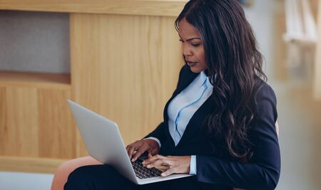 Focused young African American businesswoman working online with a laptop in the lounge of an office