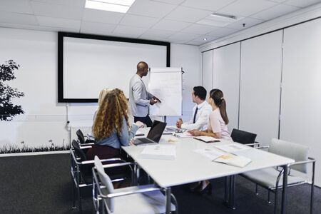 African American manager explaining business concepts to a group of staff sitting at a table in an office boardroom