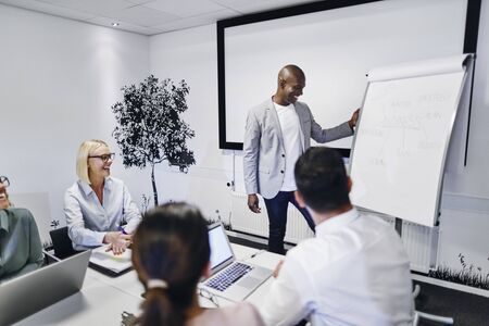 Laughing African American manager explaining business concepts to a group of staff sitting at a table in an office boardroom Banque d'images
