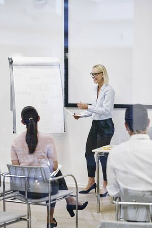 Young manager laughing while giving a flip chart presentation to staff inside of an office meeting room