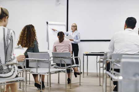 Manager pointing at a flip chart while giving a presentation to her staff in the seminar room of an office Banque d'images