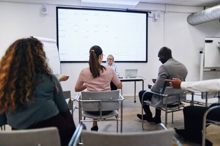 Young woman giving a projection screen presentation to a group of diverse colleagues in a meeting room