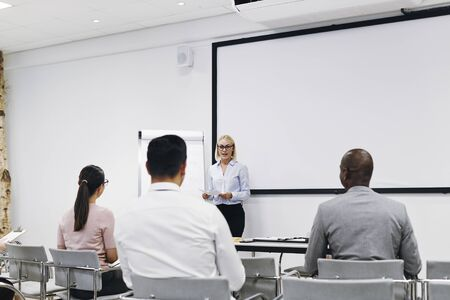 Young manager standing by a flip chart in an office meeting room giving a presentation to a diverse group of staff Banque d'images
