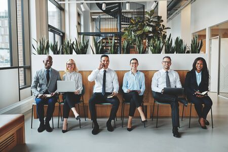 Diverse group of smiling businesspeople sitting together in a row on chairs in an office reception waiting for a meeting