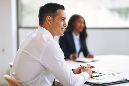 Smiling businessman sitting with a colleague at a boardroom table during a meeting in an office
