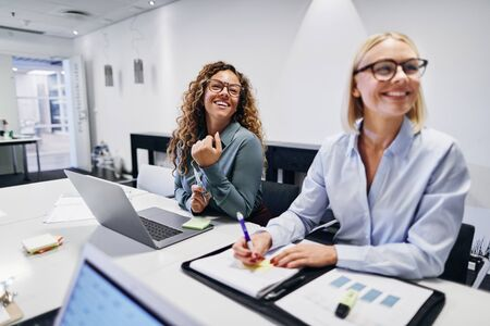 Two smiling young businesswomen sitting together at a table during a meeting in an office boardroom Banque d'images