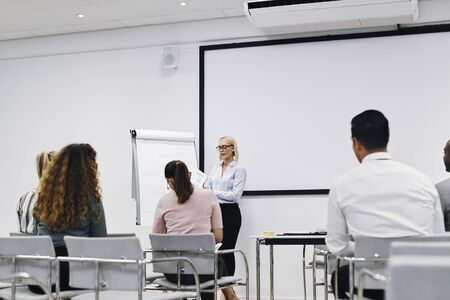 Manager reading from a document during a flip chart presentation to her staff in an office meeting room