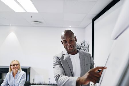 African American manager pointing at something on a flip chart during a presentation to staff in an office Banque d'images