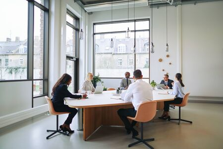 Smiling group of diverse businesspeople discussing work together during a meeting around a boardroom table in an office