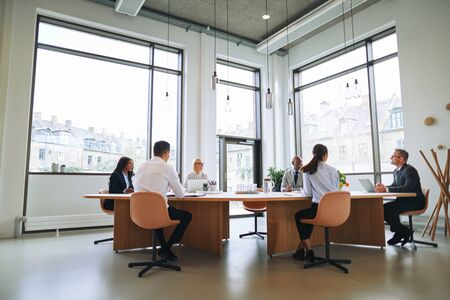 Smiling group of diverse businesspeople talking together while sitting around a boardroom table in an office