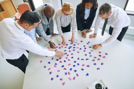 High angle of a group of diverse businesspeople standing together around an office table focused on trying to solve a jigsaw puzzle 스톡 콘텐츠