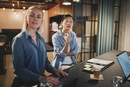 Two diverse young businesswomen listening to an unseen colleague during a meeting around a table in an office
