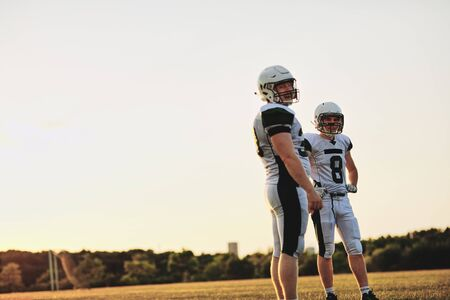 Two American football players standing on a sports field and talking after an afternoon practice
