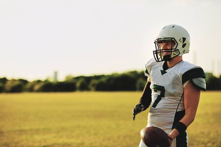 American football quarterback holding a ball during a team practice on a sports field in the afternoon 免版税图像