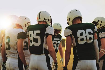 Group of young American football players standing in a huddle together before a late afternoon game 免版税图像