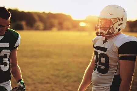 Two American football players standing on a field and talking together after a team practice in the late afternoon