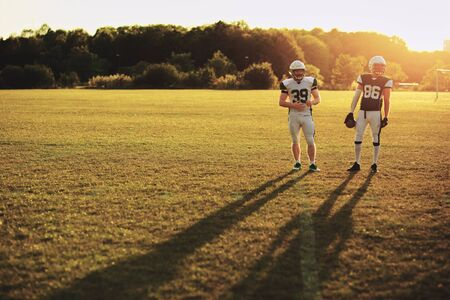 Two American football players standing together on a playing field during a lateafternoon team practice Stock Photo