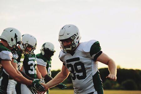 Aufgeregter American-Football-Spieler, der seinen Teamkollegen nach einem Spiel am späten Nachmittag Low Fives gibt