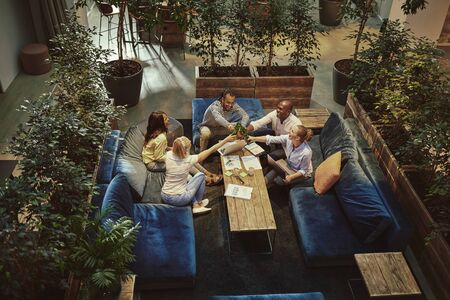 High angle of a diverse group of young businesspeople toasting together with beers after work in the lounge of an office complex Foto de archivo - 139417029