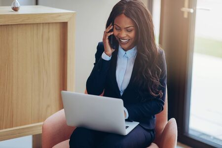 Smiling young African American businesswoman talking on her cellphone while sitting in a chair in the lounge of an office working on a laptop