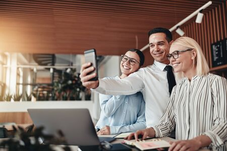 Smiling group of young businesspeople taking a selfie together while working at a table in a modern office