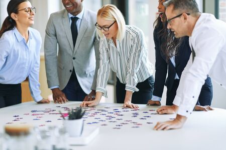 Diverse group of smiling businesspeople working together to solve a jigsaw puzzle while standing around an office table