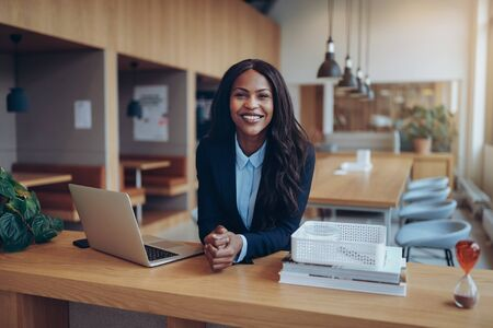 Confident young African American businesswoman smiling while leaning on a table in an office lounge working on a laptop