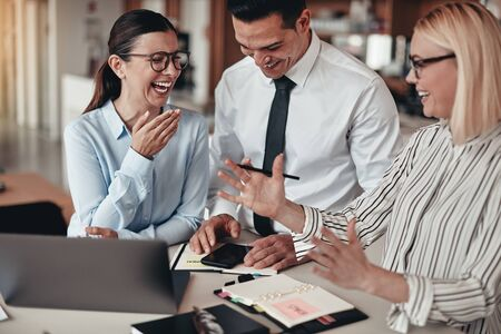 Three laughing young businesspeople looking at something on a cellphone while working together at a table in an office