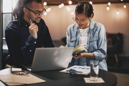 Two diverse young businesspeople smiling and going over notes together while sitting at a table in a modern office