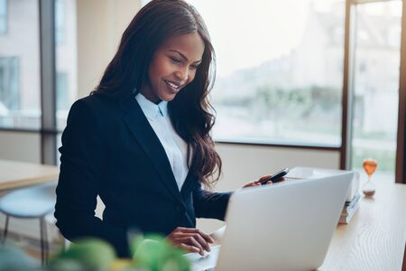 Smiling young African American businesswoman standing at a table in an office lounge reading a text message on her cellphone and working on her laptop Banque d'images