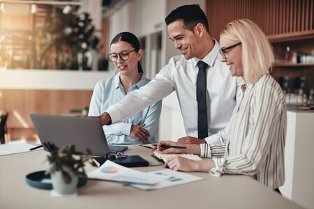 Three smiling young businesspeople standing at a table in an office going over paperwork and working on a laptop Banque d'images