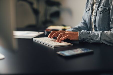 Closeup of a businesswoman typing on a computer keyboard while sitting at her desk in an office