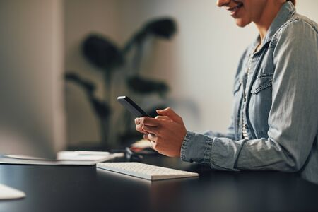Closeup of a businesswoman smiling while reading a text message on her cellphone at her desk in an office Banque d'images