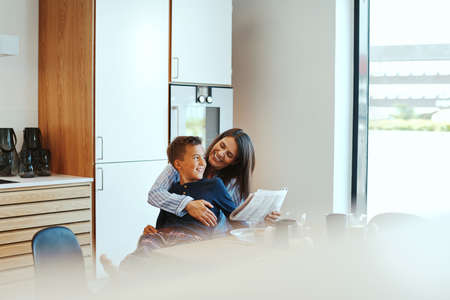 Cute little boy sitting on his mother's lap and reading the newspaper together at their kitchen table after breakfast