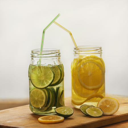 On the Board two cans of soda. Drinks - lemon and lime. Diffused light. Slices of citrus in a jar on the table. Lifestyle. White background.
