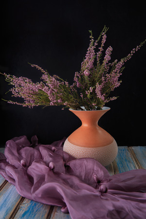 Bouquet of dry Heather in a ceramic vase on a black background. Purple wild flowers in a vase. Lilac tippet organza diagonally. Blue wood plank background. Studio light. Place for text.
