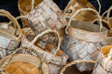 splint: Cesta de mimbre hecha de corteza de abedul sobre un fondo blanco. Artesanías eslavas nacionales. Hecho a mano en un estilo rústico. Una canasta para bayas, setas, frutas, verduras, para el hogar Foto de archivo