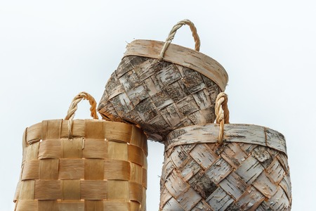 Wicker basket made of birch bark on a white background. National Slavic crafts. Handmade in a rustic style. A basket for berries, mushrooms, fruits, vegetables, for household