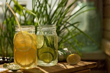 muddy: Two glass jars with lemonade on a wooden stand in a wooden house. A lot of sun. Soda in a jar with a lid. Breakfast on the grass.