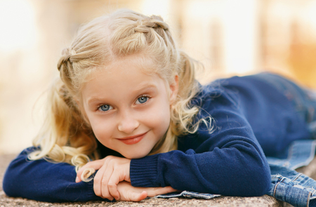 Close-up lying and looking at the camera. Girl with blond hair. Child in a blue sweater and jeans. Autumn toning. Shooting outdoors.