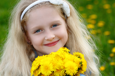 Baby girl 7 years of smiling fun. Beautiful blonde holds in her hands a bouquet of yellow flowers. The happiness concept, happy childhood.