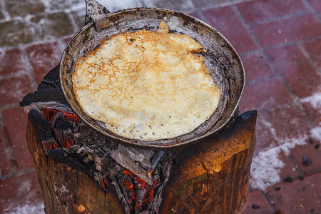 aluminium: Pancakes are fried on a hot pan. Hot the pan is burning stump. Cooking pancakes in the traditional way in a rustic style.