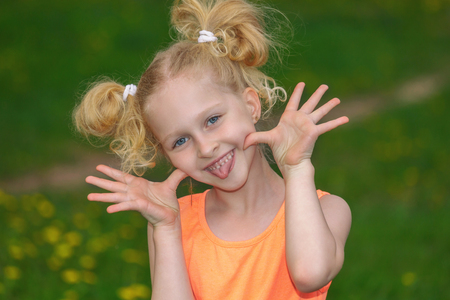 Naughty girl 7 years old portrait. The child laughs merrily and shows language. The girl in the orange dress. The concept of a happy childhood. Blonde is a trendy hairstyle. Stock Photo