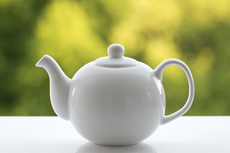White teapot on a green blurred background, closeup.