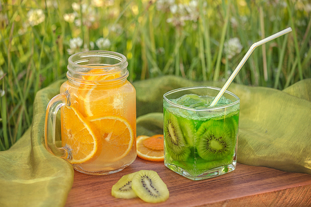 muddy: Two glass jars with lemonade on a wooden stand on the grass. Soda in a jar with a lid. Breakfast on the grass.