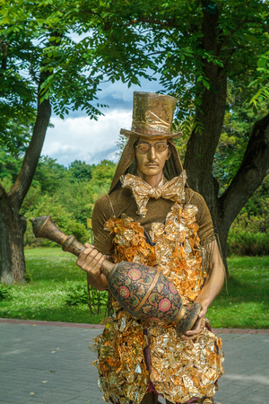 16.07.2017.Minsk Belarus, and Botanical gardens. A living sculpture. The male attracts the attention of tourists in the theatrical costume in the Park. A man with Golden skin dressed in Oriental style