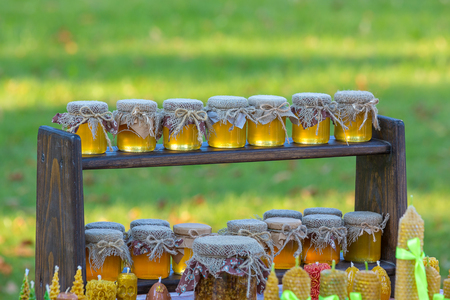 sold small: Small jars of honey are on a wooden shelf, Honey is sold at the fair of honey. Beautiful evening light.