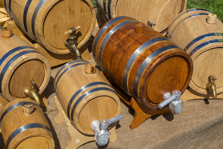 Small wine casks are made with old technology and sold at the fair. 7 oak barrels with hoops. Stock Photo