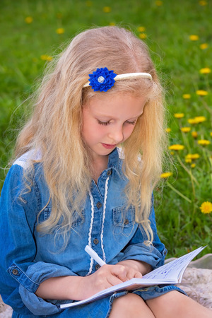 Smart, studious girl of 7 years. A child writes with a pen in a notebook. Baby is learning to write first words. The girl has blond hair, she sits on the grass among the dandelions and looking forward.