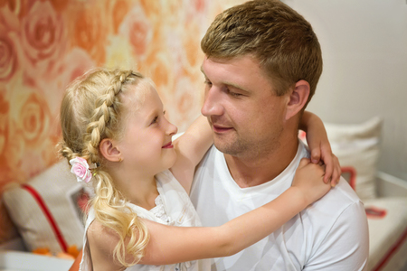 Portrait of a little girl and her dad. Beautiful girl tenderly looks at his father. Loving a child hugs his father. The concept of Fathers Day. Soft focus.